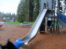 kid in blue sweater falling off slide